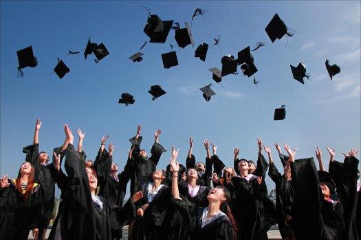 Graduates throwing cap into the air in celebration
