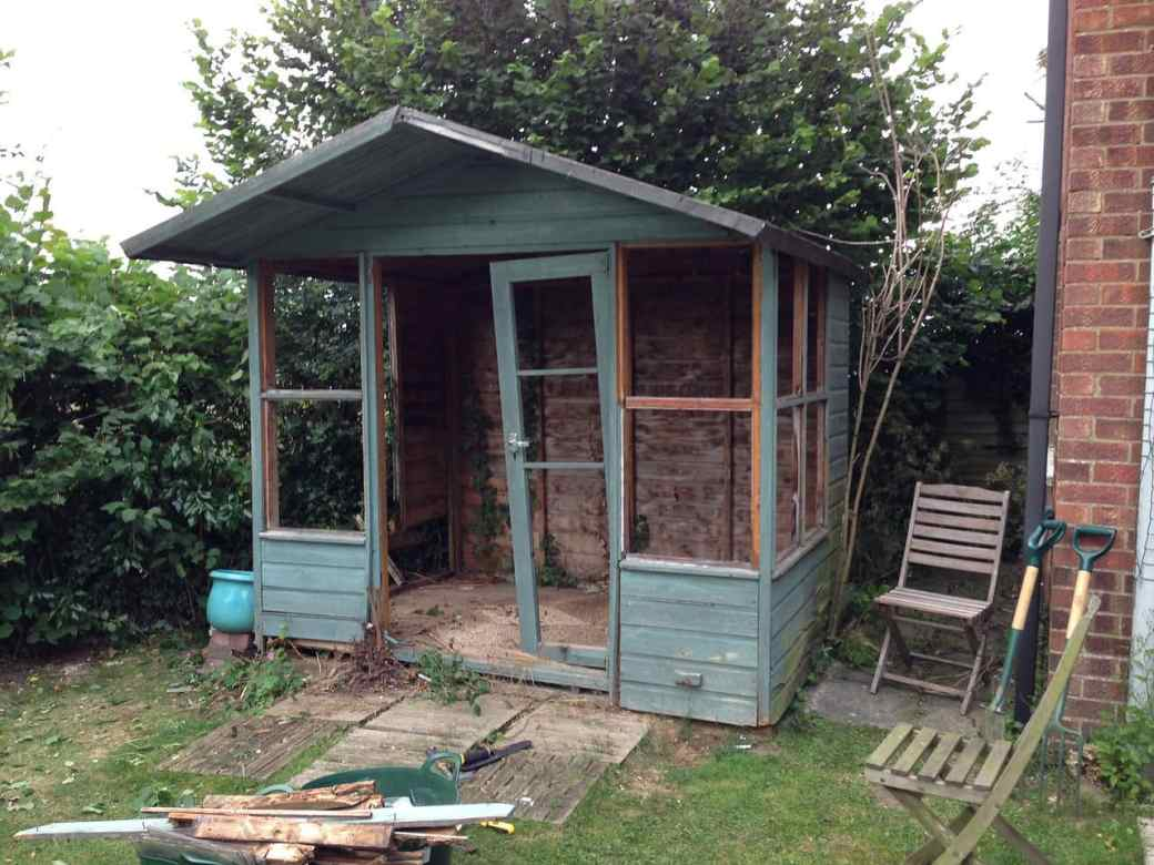 A rotten wooden summerhouse, in the midst of being demolished