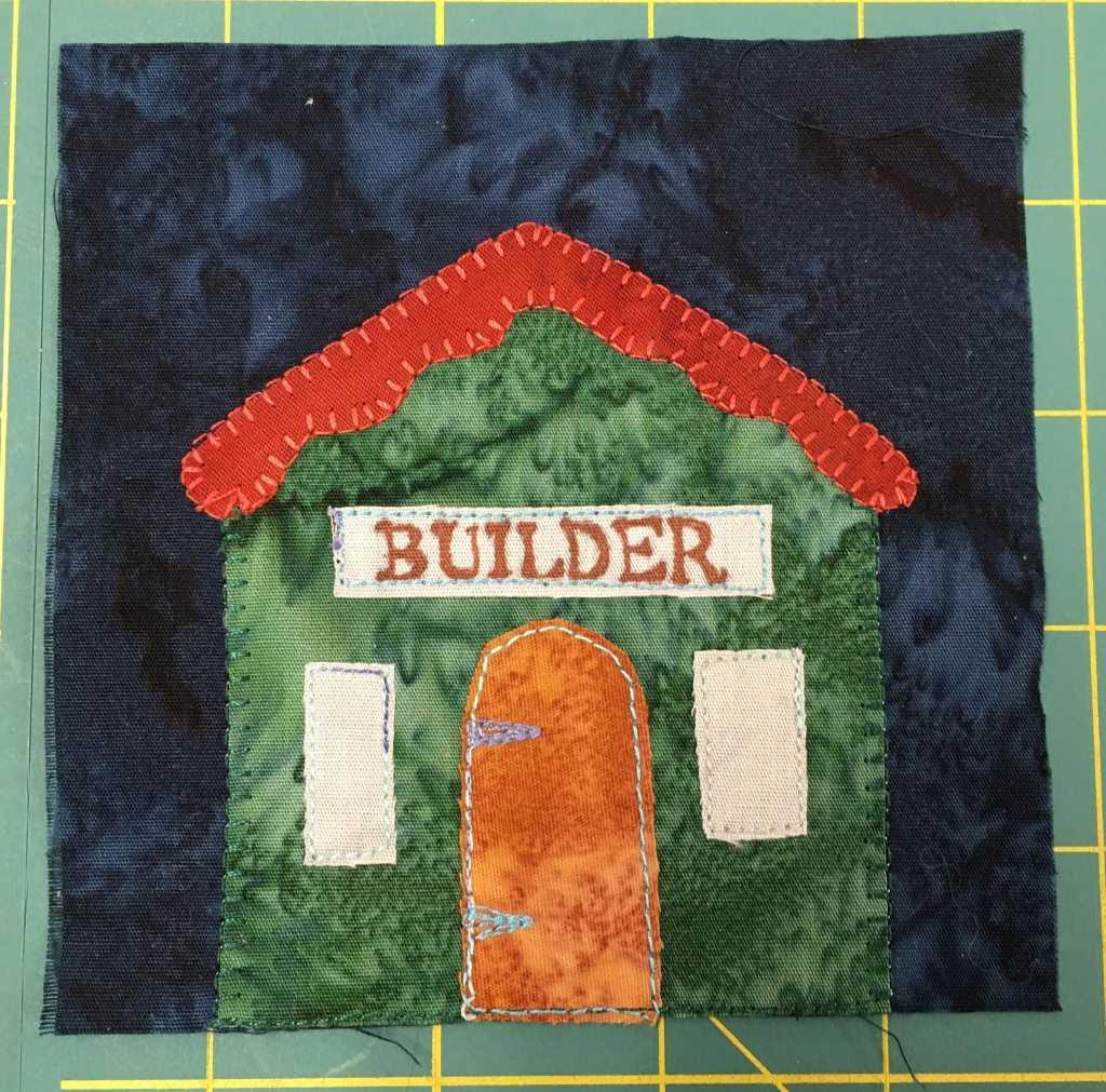 "A quilt block with a dark blue background showing a building with a red angular roof. It has the word ""builder"" on a sign above the golden-brown door."