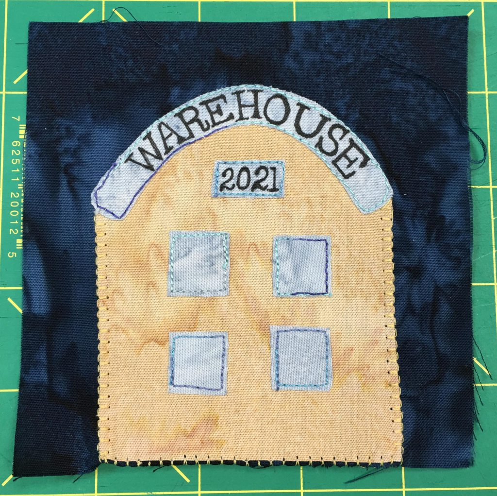 """This quilt block shows a yelow building with a domed roof. It has four blue-silver windows, the word """"Warehouse"""" on the top, and a sign reading """"2021."""""""
