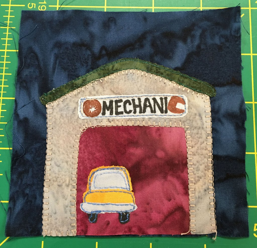 This quilt block shows a garage against a dark background. The inside of the garage is a rich red and an orange car is inside.