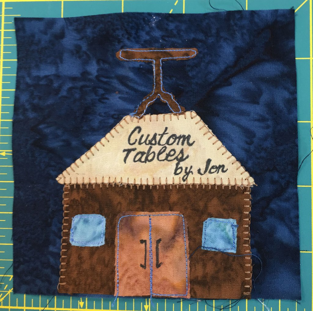 """This quilt block depicts a building with a table on top. The sign on the front reads """"Custom Tables By Jon"""" There are blue windows on the sides of two orange double doors."""