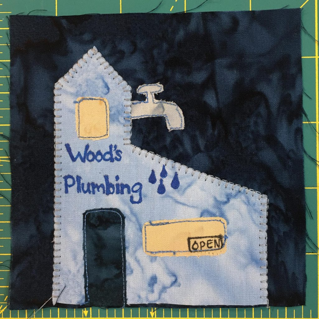 """This quilt block shows a blue building with a faucet coming out of the top column. It is labeld """"Wood's Plumbing"""" and has a tall dark door and a two yellow windows."""