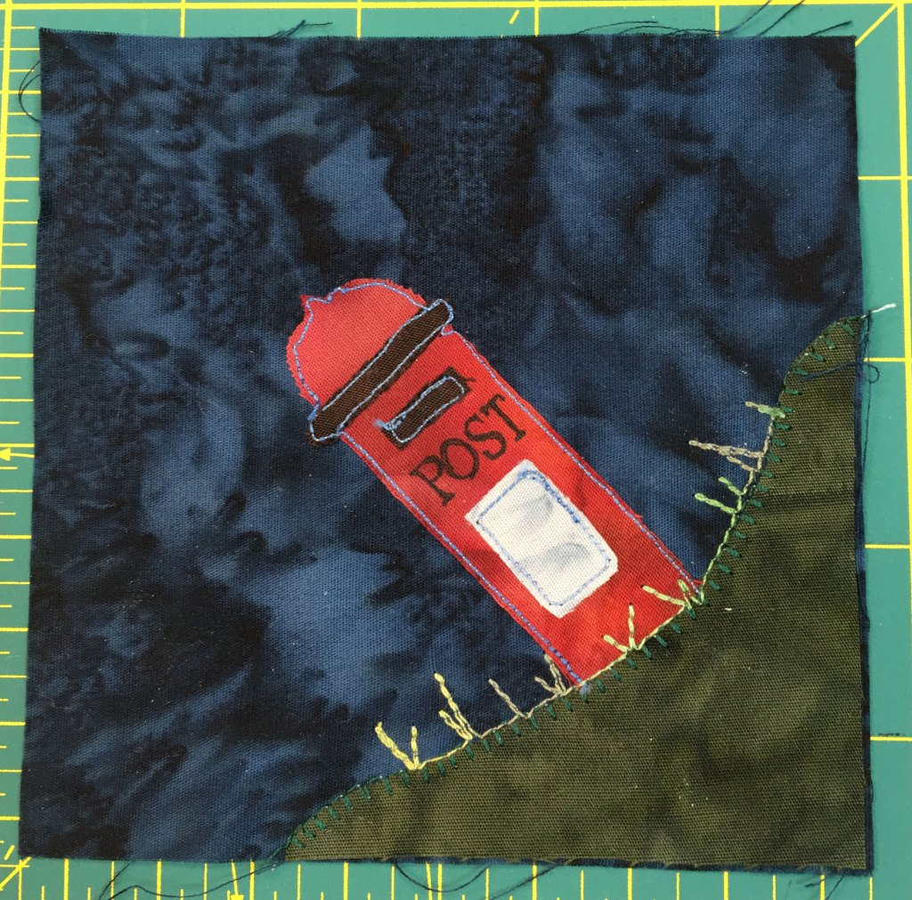 This quilt block shows an English style postbox, or mailbox, in the bottom right on a mound of grass. It is red and white.