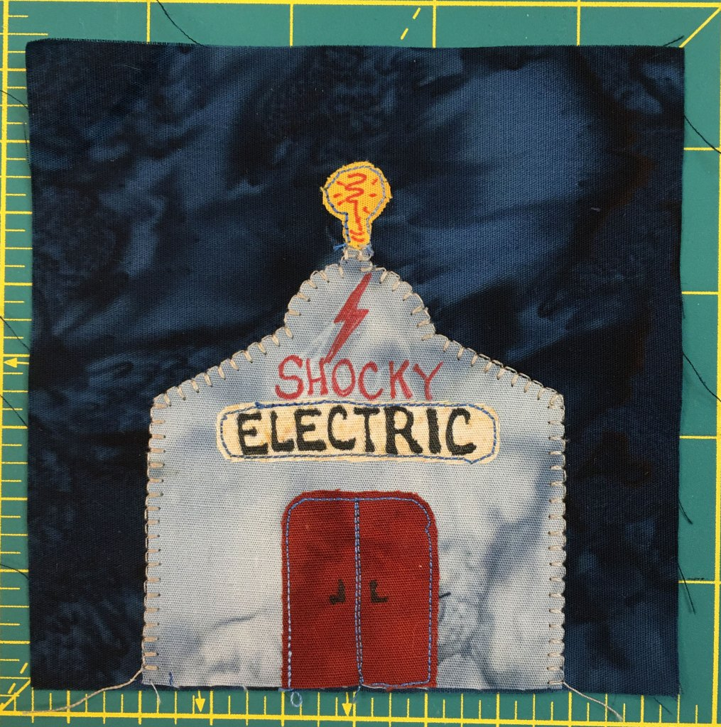 """This quilt block shows a gray metal building against a dark background. It has red double doors, and a lightbulb on the top of it. The front reads, """"Shocky Electric"""" under a red lightning bolt."""
