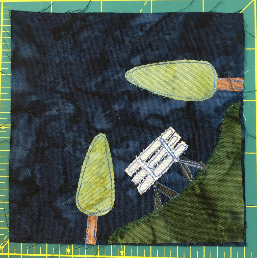 This quilt block shows a patch of grass in the bottom right with a white bench and two trees, one vertical and one horizontal. The patch of grass overlaps the corner on the botom and right sides.
