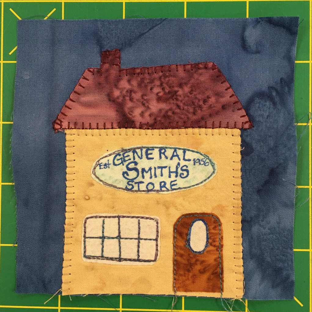 """This quilt block shows a yellow house with a deep red roof and chimney. On the front a sign reads, """"Smith's General Store Est. 1956."""" There is a red door on the right, and a large multi-paneled window on the left."""