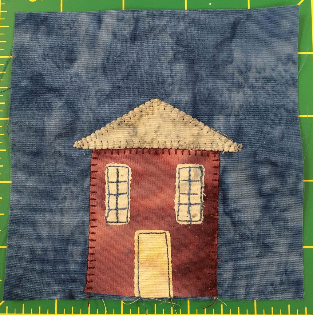 This quilt block shows an orange-red house against a darker blue background. The house has two tall window on the left and right, and a tall yellow door in the middle giving it a look of surprise.