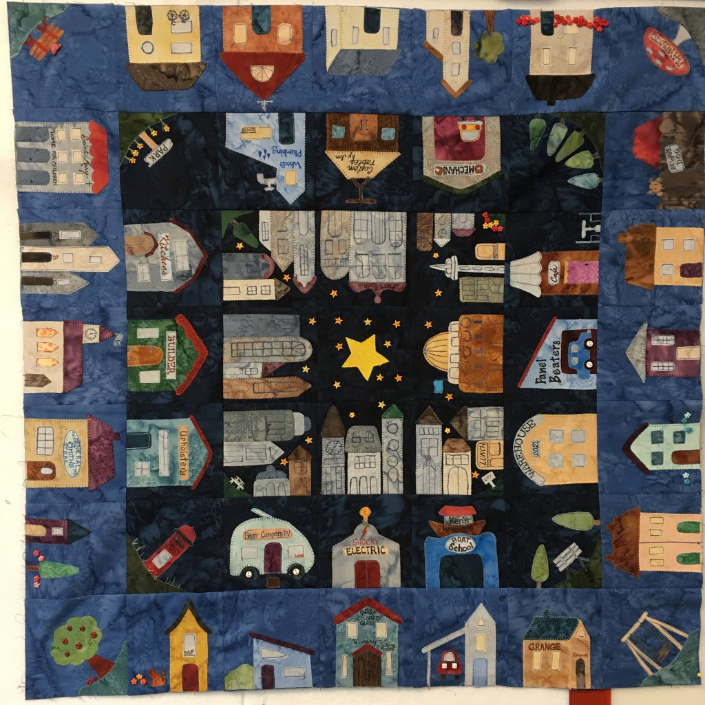 This shows a quilt with three outer rings full of buildings and a star in the center.