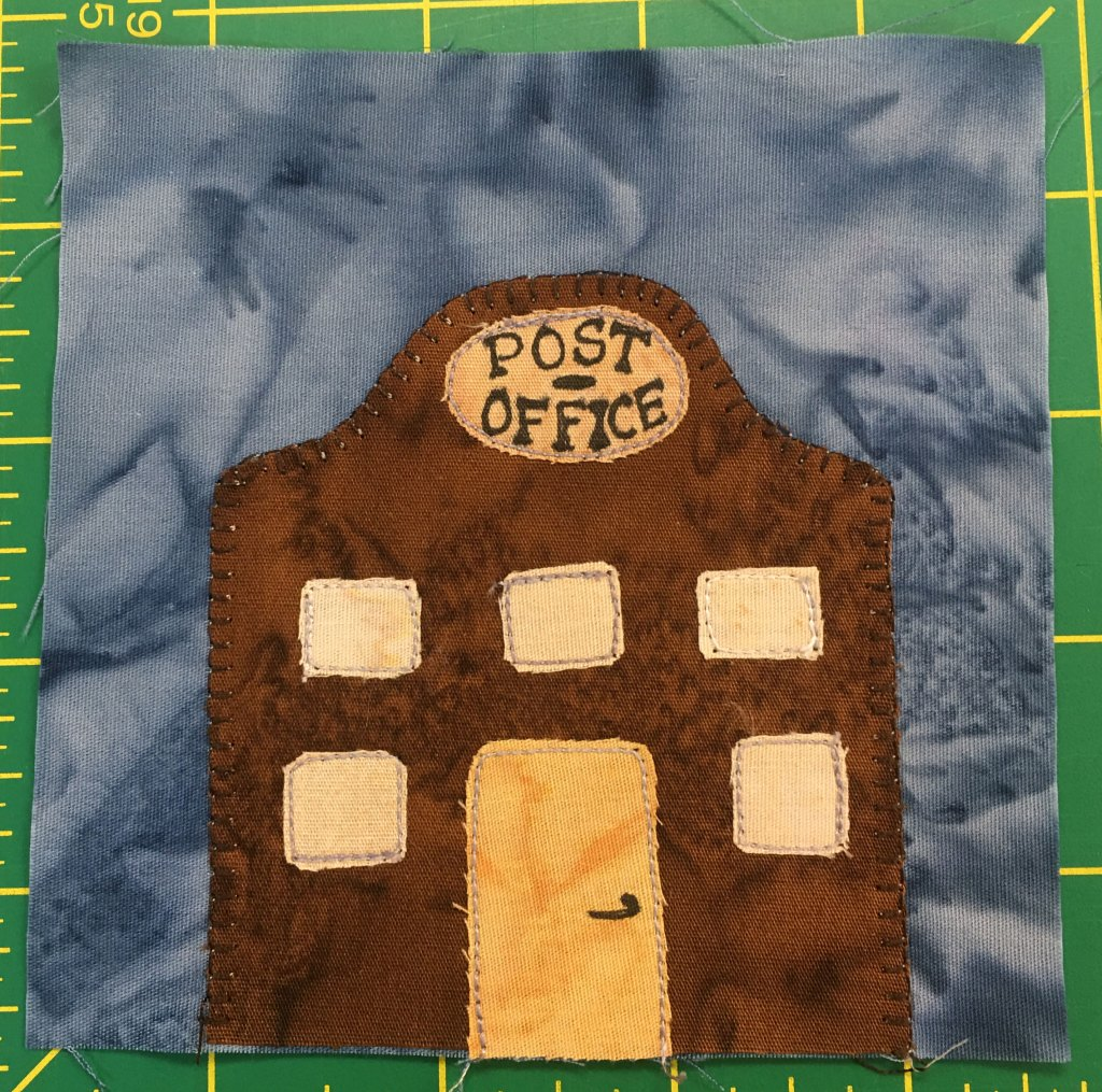 """This quilt block shows a tall brown building with a curve shaped roof. In the center of the roof is a round sign that says, """"Post Office."""" There are five windows, three in a row on the second floor, and the door is yellow with a handlebar doorknob."""