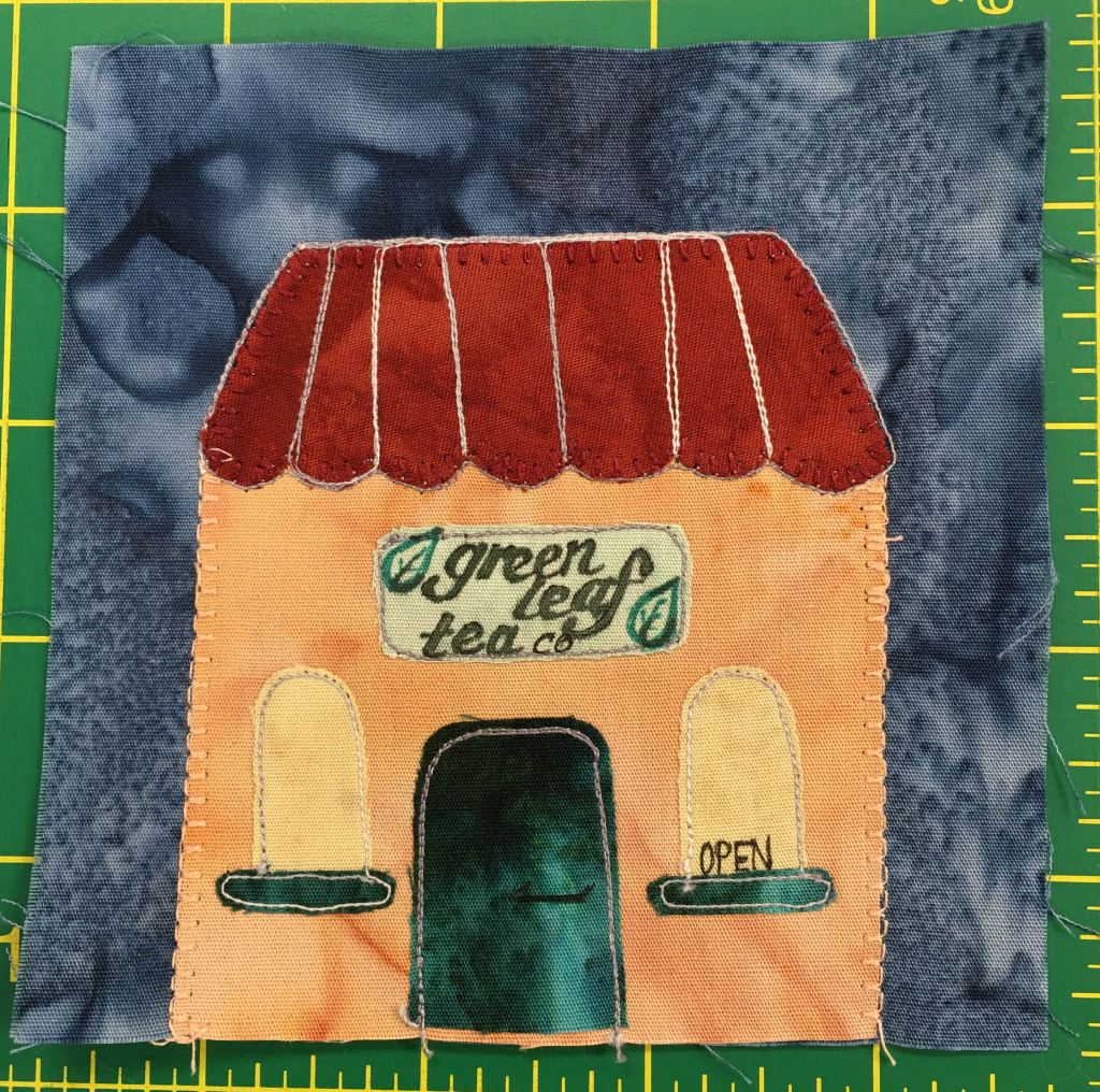 """This quilt block shows an orange building with two domed yellow windows on either side of the green door. The windows are framed on the bottom by the same green trim. The roof is paneled and red. A sign with leaves on it reads, """"Grean Leaf Tea Co."""" and the right side window has the word """"Open"""" sitting inside it."""