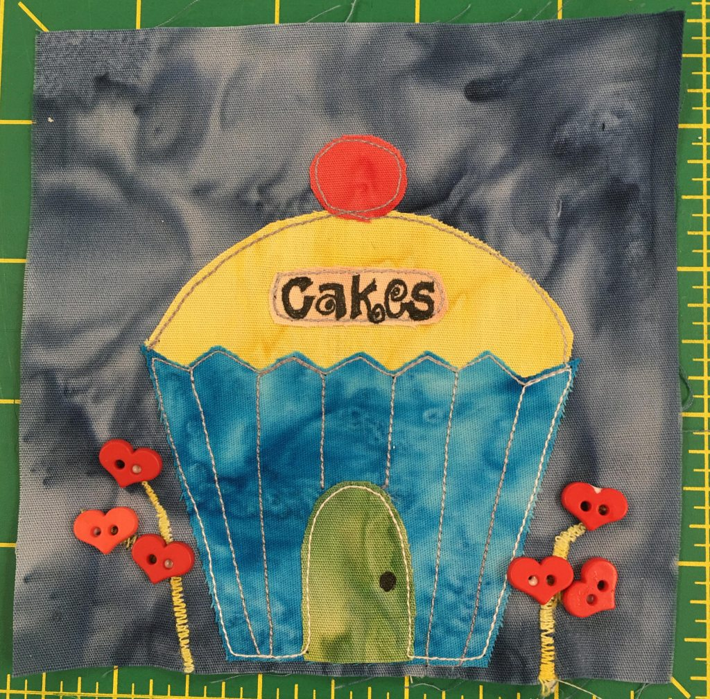 "This quilt block shows a blue and yellow cupcake shaped building. The front dor is round and green, while the building body looks liek a blue cupcake wrapper. The roof is a dome of yellow with a red cherry on top. To the left and right are some flowers shown with heart shaped buttons. The sign on the yellow dome says, ""Cakes"" in curly letters."