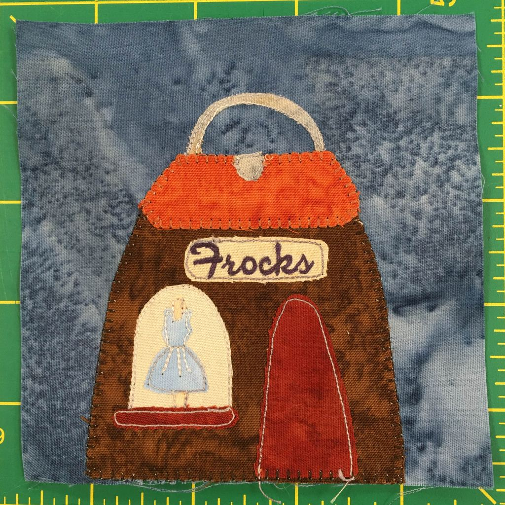 """This quilt block shows a building shaped like a handbag. It is brown with an orange flap roof, a gray clasp and a gray handle. In the display window on the left of the building is a blue dres, and to the right of that a red door.  There is a sign on the front that reads, """"Frocks."""""""