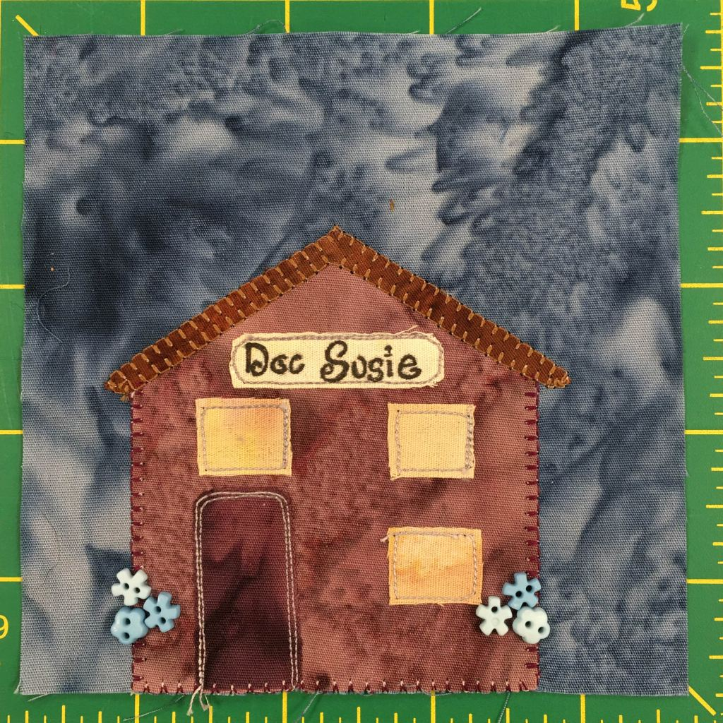 """This quilt block shows a brown building with three golden windows. Two vertically on the right side, and one above the darker brown door. The roof is a simple angled roof. Under the rood if a sign in cursive that says, """"Doc Susie."""" There are little blue and white flowers on each side of the building denoted by little colorful and appropriately shaped buttons."""