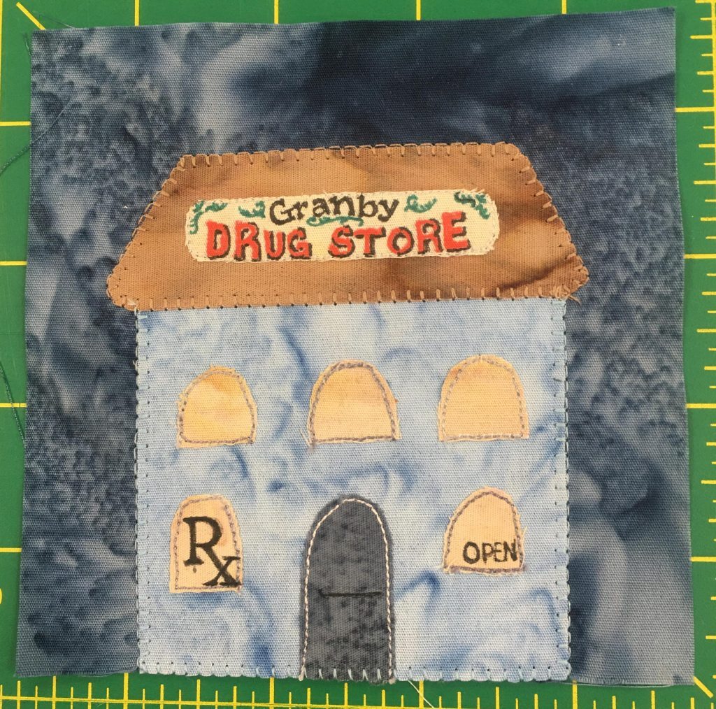 """This quilt block shows a tall building with a trapezoid shaped orange roof that has a sign on the front reading, """"Graby Drug Store"""" with decorations. The windows are light yellow, and in the left side first floor window is the symbol for a prescription or pharmacy, and in the right window is the word """"open"""". The front door is in the center and gray."""
