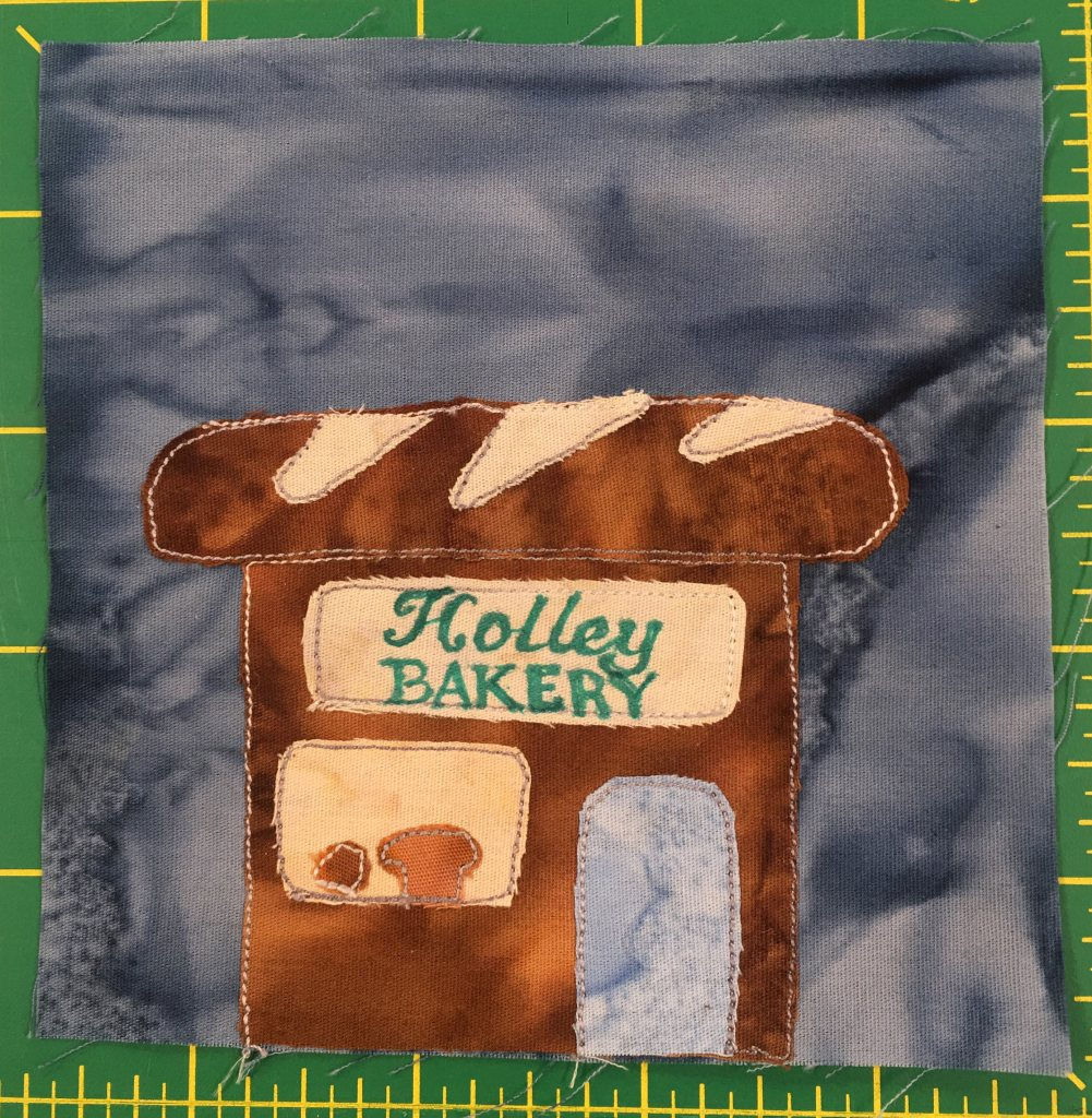 """This quilt block shows a brown building with a roof in the shape of a bread loaf. The sign on the front reads, """"Holley Bakery."""" In the window on the right are loaves of bread, and to the right is an open door."""