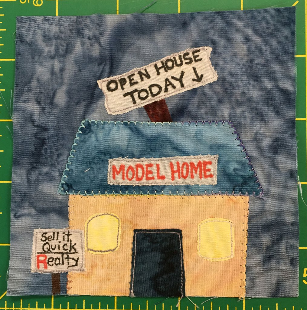 """This quilt block shows a square light orange building with a rhombus shaped dark blue roof. There's a dark door in the middle and a yellow window on either side. A sign on a post stuck in the ground to the left of the building reads, """"Sell It Quick Realty."""" Above the door and on the roof is a sign that says, """"Model Home"""" in capital red letters. There's a big mock sign that looks like it's stuck on a post that's in the roof that reads, """"Open House Today!"""""""