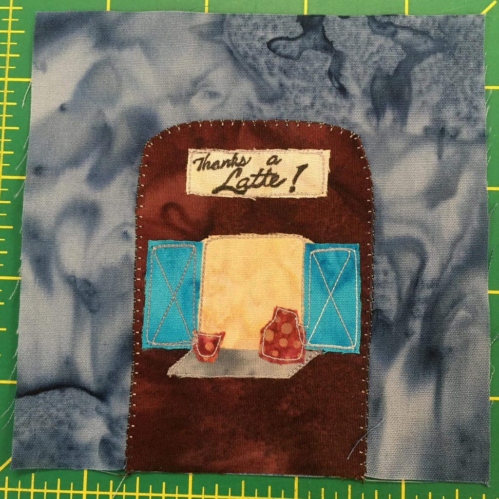 """This quilt block shows an enclosed coffee stand. On the front is a big window that's open with two blue door """"flaps"""" on either side. There's a counter sticking out from the yellow window with two coffee containers on it. At the top of the dark brown structure is a sign with stylized letters that say, """"Thanks A Latte!"""""""