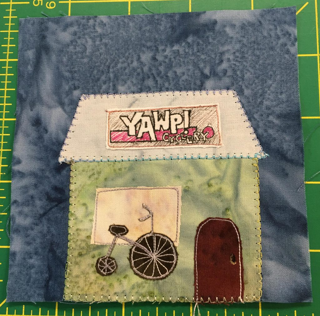 """This quilt block shows a sqaure building with a rhombus shaped roof. The buiding is a light blue green and has a brown rounded door. Next to the door and in front of a large rectangle window is a penny-farthing otherwise known as an ordinary (an old stylel bike with a huge front wheel). The sign on the roof is in an 80s style and reads, """"Yawp! Cyclery."""""""
