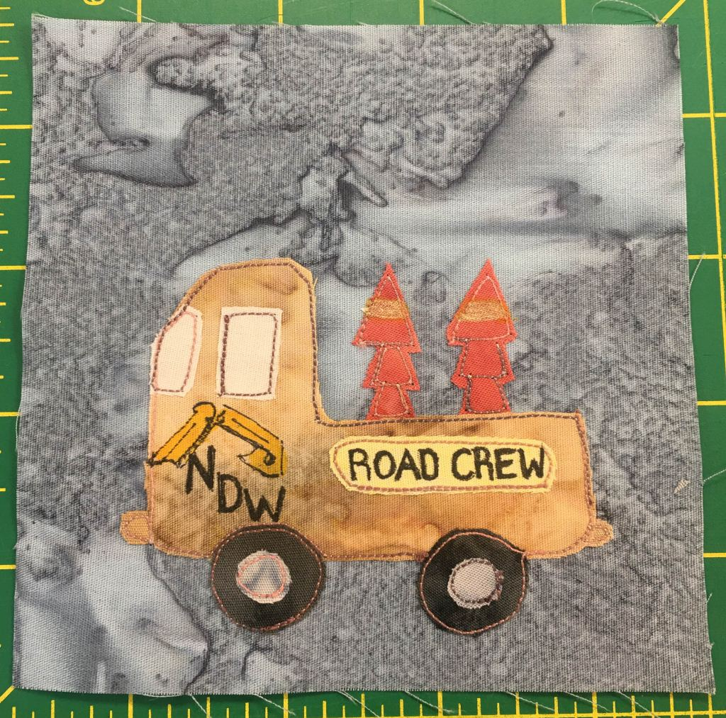 """This quilt block shows the side-view of a truck with a deep bed that contains stacked orange traffic cones. On the side of the truck are the words, """"Road Crew,"""" alongside the words and logo for """"Nick's Dirt Works."""" Rounding out the truck are two sets of black wheels."""