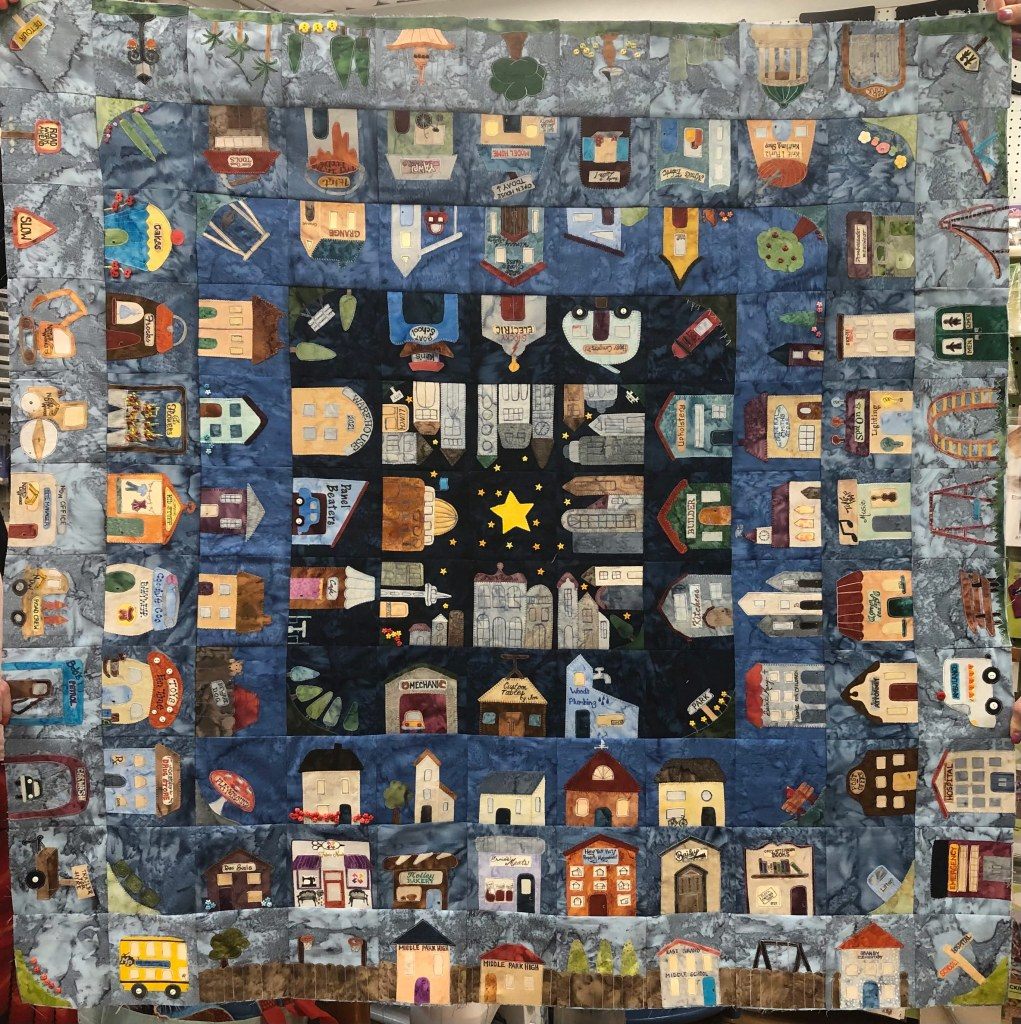 This shows the quilt as it's constructed so far. There are five rounds and a center square featuring a star. As each square round progresses outward the background gets lighter, as if the sun is rising.