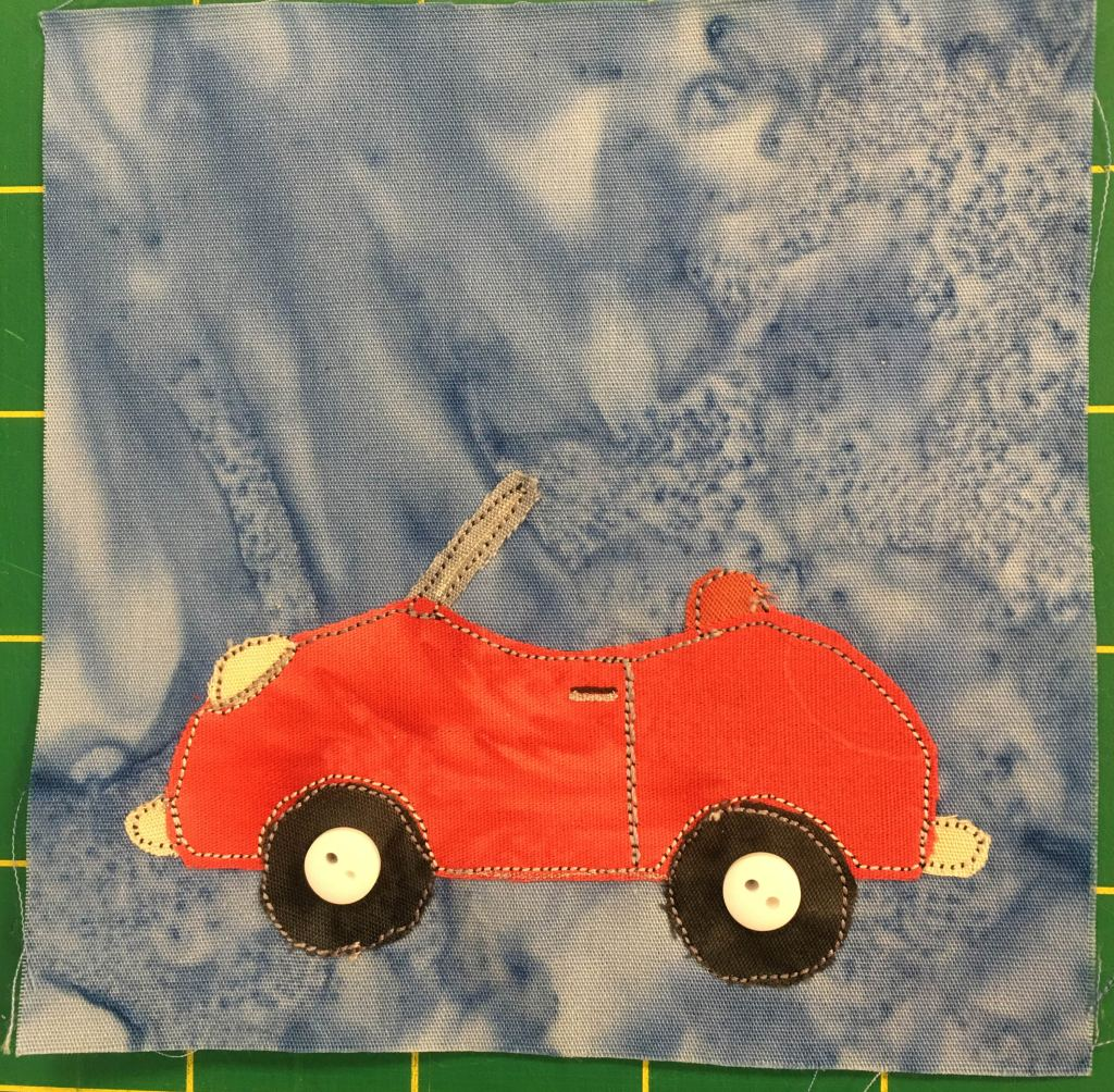 This quilt block shows a red little buggy convertible car with the roof off against a light blue background. The car itself is from a side view, with two dark wheels whose hubcaps are represented by two small white two-holed buttons. The red car only has one set of doors and no back seat.