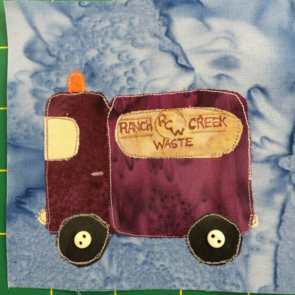 """This quilt block shows a purple or deep marron square truck whose bed is as tall and big as its cab. There is an orange warning light on top of the cab. The window of the cab is a light yellow. The bed has a yellow sign on the side with a logo that reads, """"Ranch Creek Waste."""" There are two dark wheels on the bottom with buttons in the center of them to indicate the axle. This is all against a light blue background."""