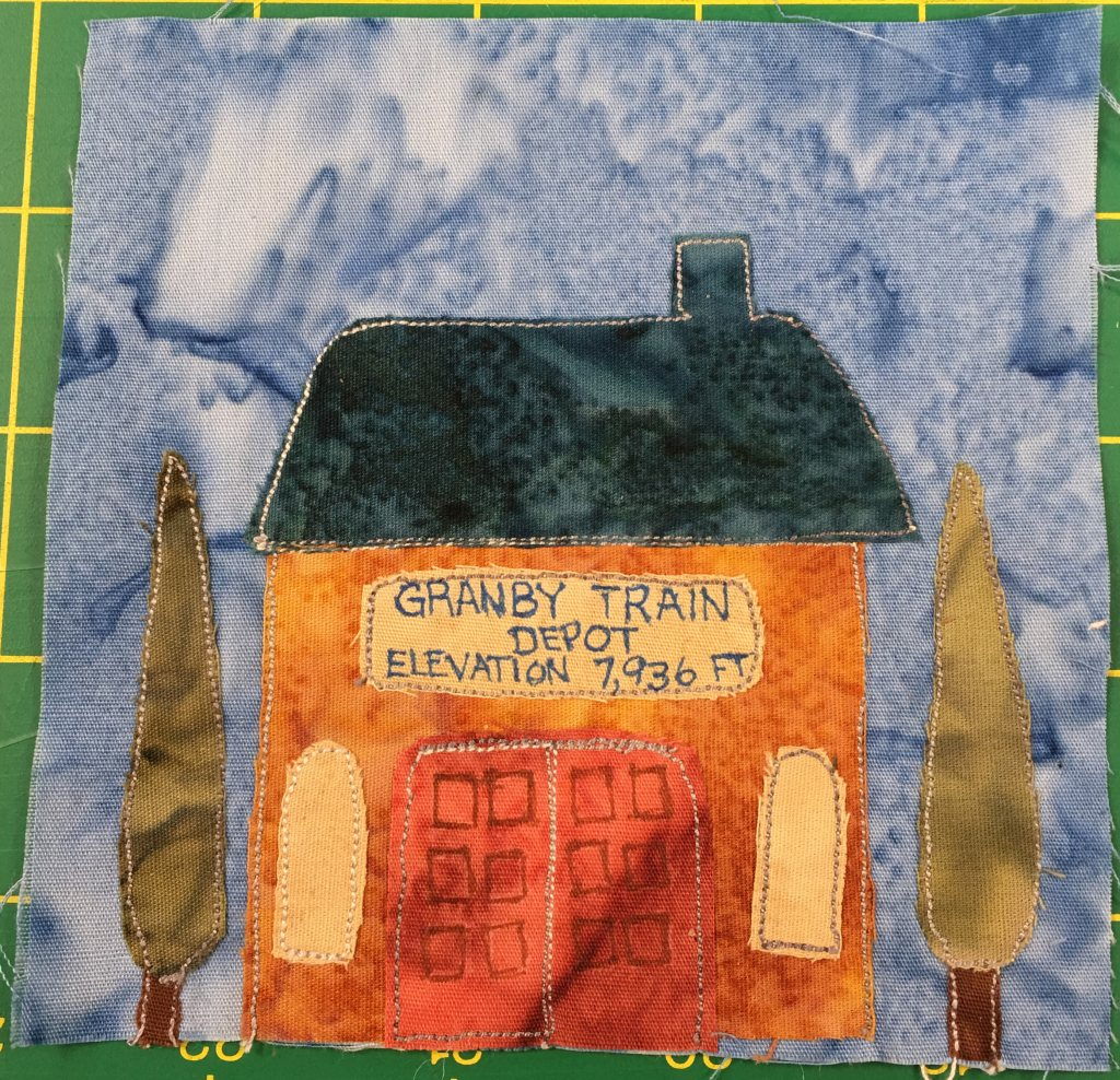 """This quilt block shows a train depot with two poplar trees on either side. The train depot's roof is a dark blue with a little smoke stack coming out on the right. The roof itself is a large trapezoid shape. The building below is a bright orange square. Two large red doors are in the center with squares on them, and to either side of those doors are light yellow windows. Above the large double doors is a sign that reads in blue against light yellow, """"Granby Train Depot, Elevation 7,936 ft."""""""
