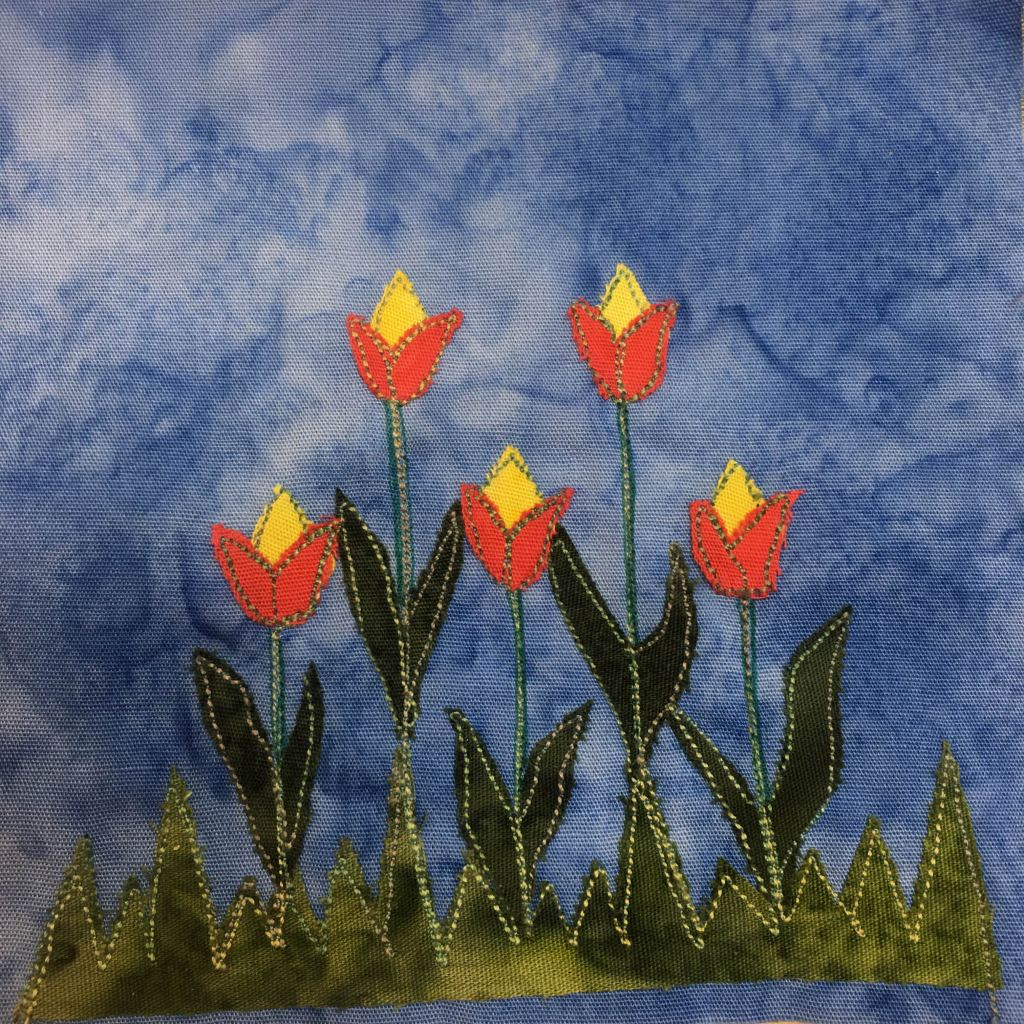 This quilt block shows a bunch of flowers. Five tulip looking flowers extend upwards from a jagged piece of green fabric made to look like grass. The stalks of the flowers are pen and stitching. The leaves that point upwards, two for each flower on each side are a darker green with a light green stitching outline. The tops of the flowers, the bulbs, are a bright orange at the base, with a yellow part sticking out the top, much like a tulip.