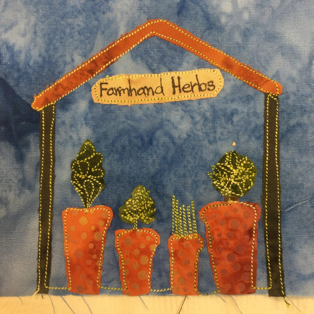 This quilt block shows a roadside herb stand. The stand is made up of two dark sticks on the side and a triangular thin ceiling that is orange. Inside the stand are four pots in a row, each a piece of orange polka-dotted duotone fabric. On the top of each pot is a piece of green fabric. Each piece is a different shape and heavily stitched to indicate its shape. The shack and pots are outlined with a bright yellow stitching. This is all against a blut salmon-patterned background.