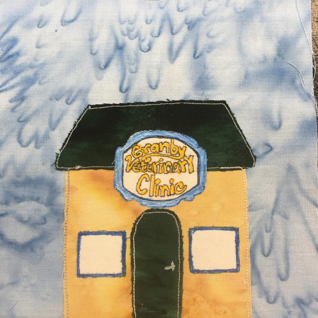 """This quilt block shows a yellow square building with a trapezoid roof. The roof and the door are a dark green-blue. The door is in the center of the building with two white square windows on either side. The white windows are outlined with blue pen. The big draw to the block though is the belt-buckle like sign above the door. It's a huge blue bordered fancy sign with stylized yellow lettering that reads, """"Granby Veterinary Clinic""""."""