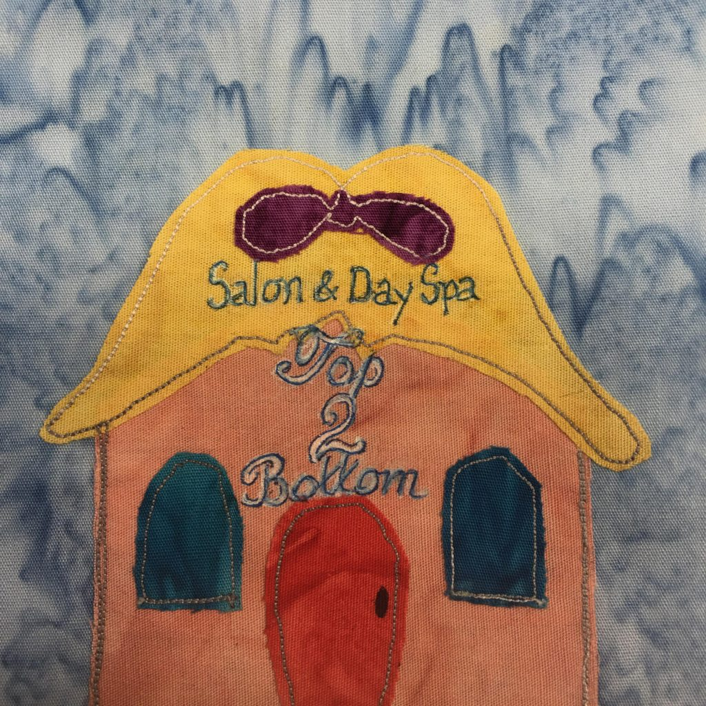 """This quilt block shows a square building but with an outlandish roof. The roof looks like hair sitting on someone's head with a purple bow in it. The hair is yellow itself. On the hair and the building are the words, """"Salong & Day Spa Top 2 Bottom"""" in blue pen with white highlights/outlines. Below the yellow hair is a pink building with dark blue rounded windows on either side to eh center red door. All of the fabric pieces are outlined with a gray stitching. The door is also fairly rounded. This is all against a light blue salmon-patterned bacground."""