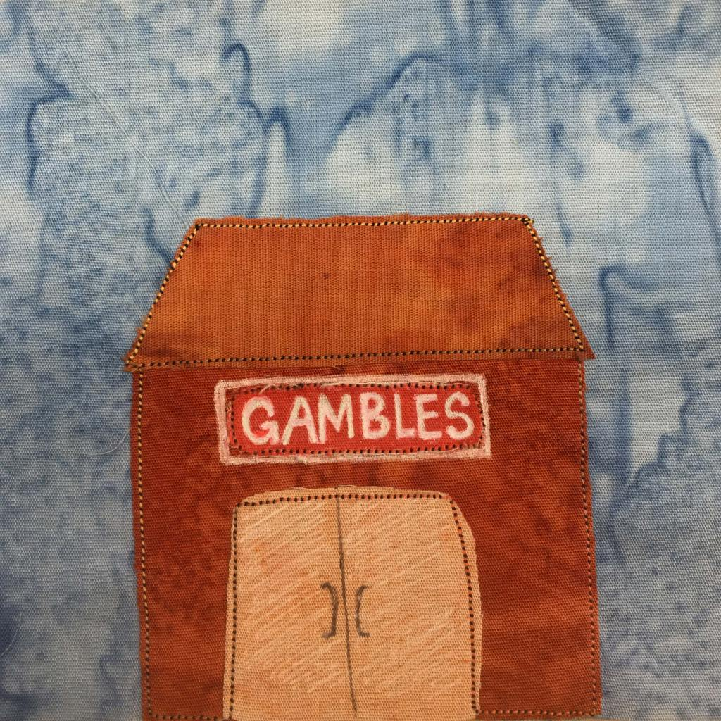 """This quilt block shows a very orange building with an orange roof and a light orange glass door (shaded with white pen). The sign above the double doors is red with a white and black border. It reads, """"Gambles"""" in white pen in bold letters across it. All the fabric pieces are outlined by an orange and black stitching."""