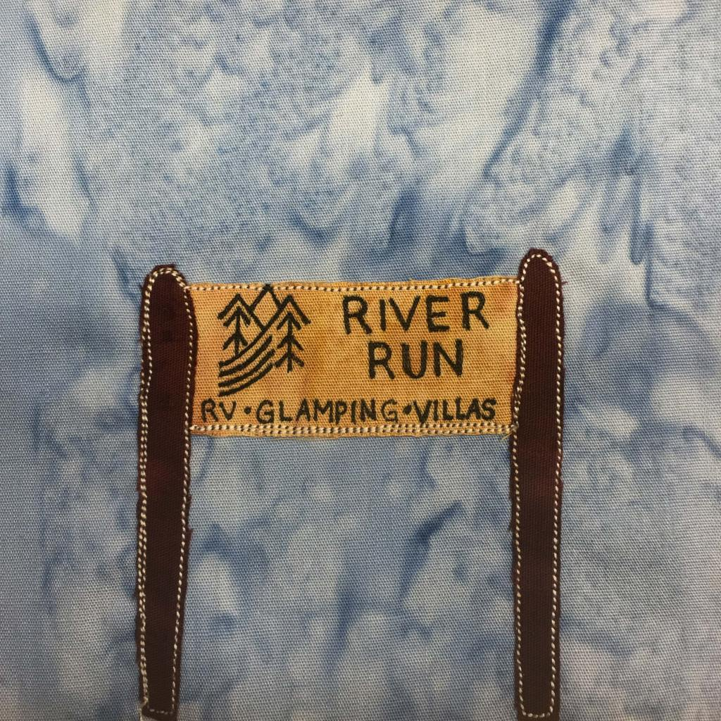 """This quilt block shows a sign like you'd see on the side of the road. The sign is between two dark brown poles. The sign itself is a dark yellow with black pen writing on it. There is a logo with mountains, trees, and what looks like a river. Next to the logo in black pen are the words, """"River Run."""" Under both the logo and the larger words are the words, """"RV • Glamping • Villas"""". Each piece of fabric is outlined with a white colored stitching. This is all against the standard blue salmon-patterned background."""