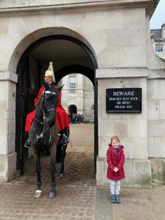 Baby standing next to horse guard box on Whitehall in London