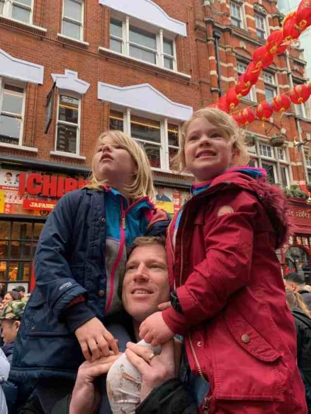 Children sat on dad's shoulders in Chinatown, London
