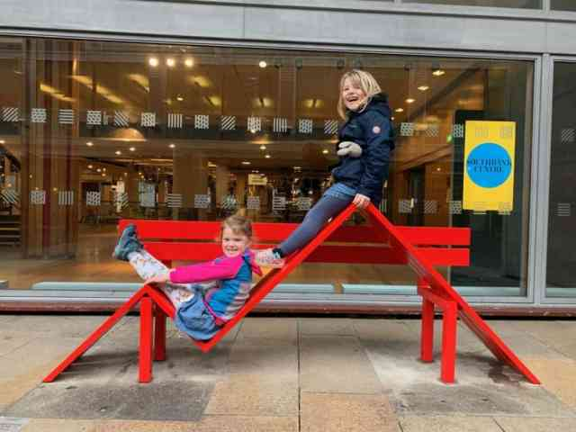 Kids sat on bench sculpture outside Southbank Centre in London