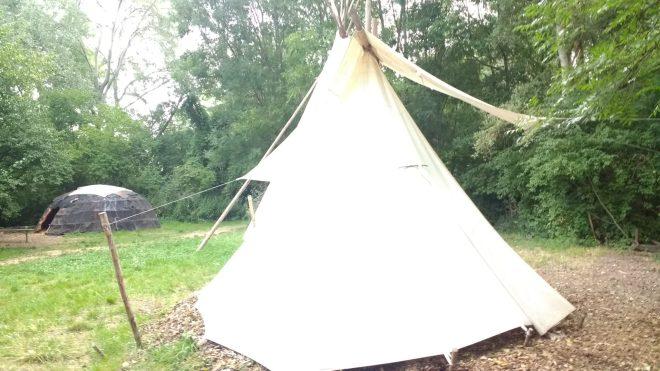 Petit tipee et à l'arriere plan un abri préhistorique au Village Lacustre
