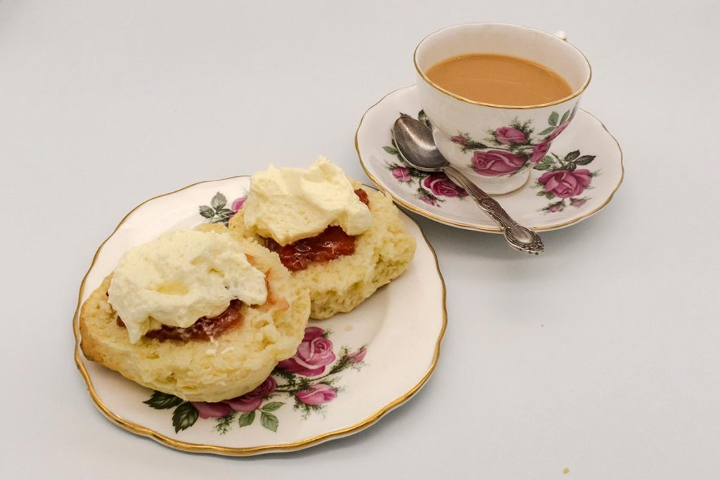 A cup of tea with a plates of scones jam and cream