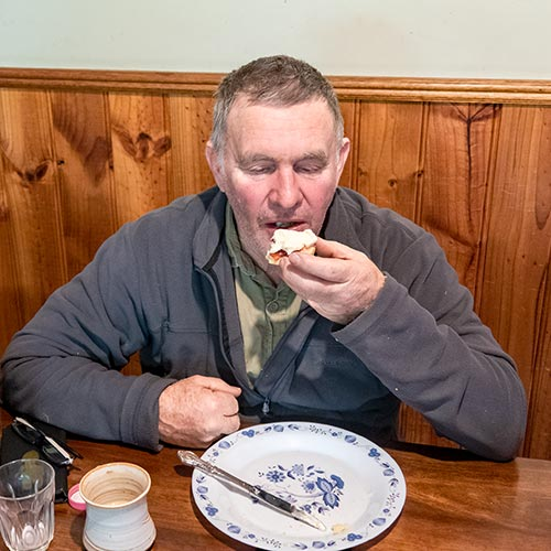 Graham eating a cream-covered scone at the kitchen table