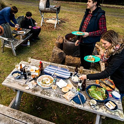 A group pf people are enjoying a selection of foods displayed on a timber picnic table at an outdoor bar-be-que.
