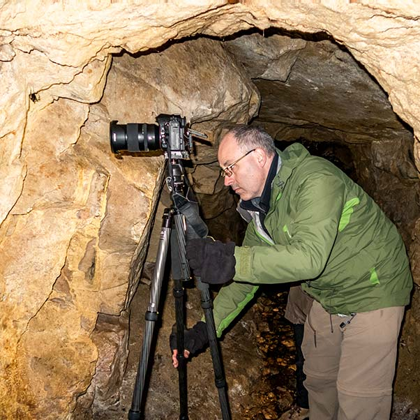 Inside a cave a photographer has set up with his tripod to photograph a large black cave spider.