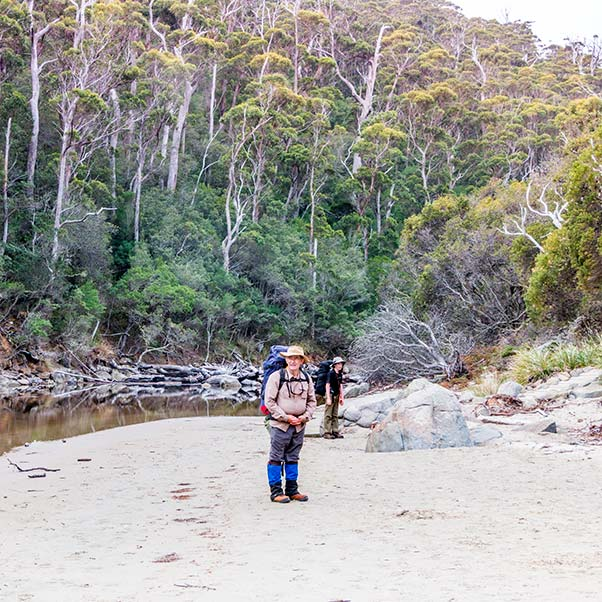 Graham and James standing with their backpacks on, Denmans Cove beach, Tasmania