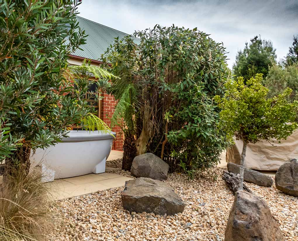 This is the exterior of Fon Hock studio cottage at Tin Dragon Cottages showing the outdoor spa bath surrounded by shrubs.