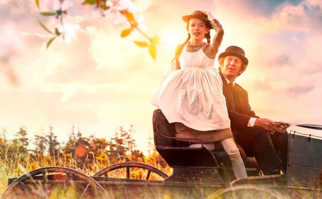 Anne de pé na carroça com Matthew segurando seu chapéu, chegando em Green Gable.