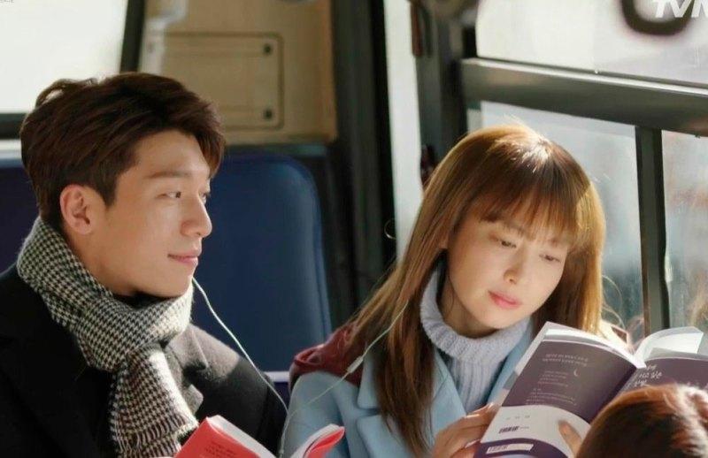 Dan-i e Seo-joon no ônibus. Dan-i lê um livro e divide um fone de ouvido com Seo-joon que olha todo apaixonado para ela.