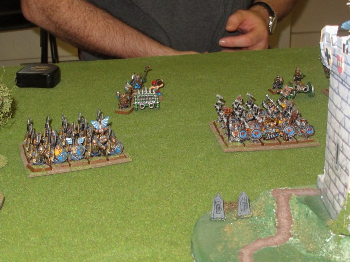 Dwarf warriors (left) and Ironbreakers (right) advance, leaving lanes for their arty to throw hurt down. The objective tower is just in the right of shot.
