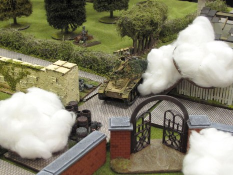 """Amid furious attempts by the 2"""" mortar to blind it, the SP howitzer rumbles up the road, pounding the houses of Ranville into rubble"""