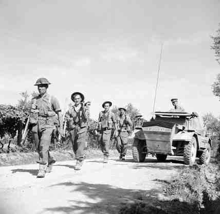 British infantry move past a Dingo recce vehicle
