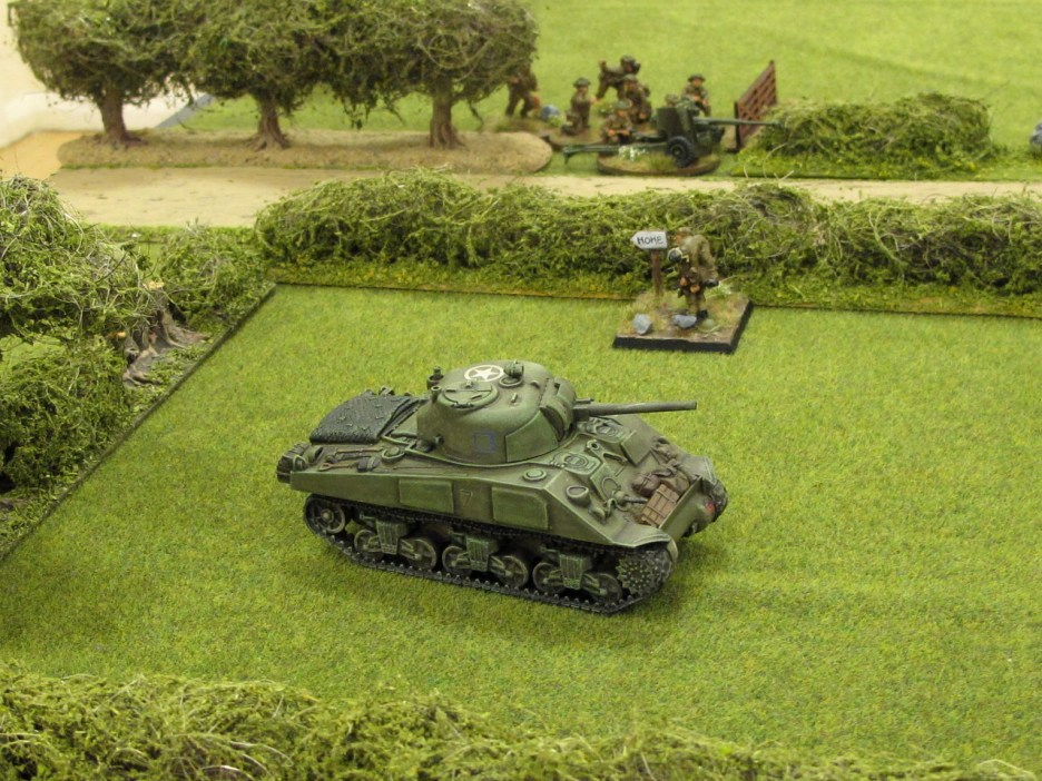 A Sherman moves up in cover while the AT gun watches the road